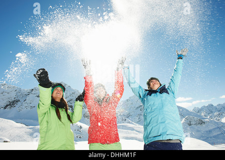 Female friends throwing snow mid air, Kuhtai, Austria - Stock Photo