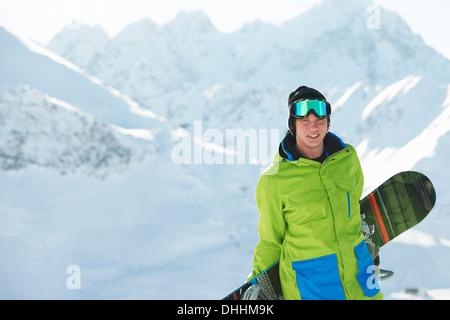 Young man holding snowboard, Kuhtai, Austria - Stock Photo