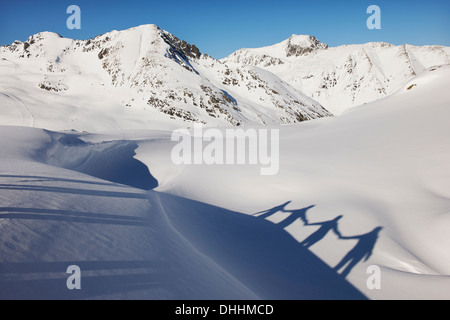 Shadow of four friends holding hands in snow, Kuhtai, Austria - Stock Photo