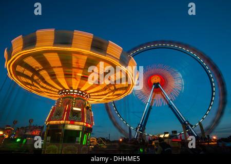 Chair-o-plane or wave swinger and a ferris wheel at dusk, Octoberfest, Munich, Upper Bavaria, Bavaria, Germany - Stock Photo