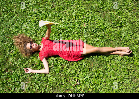 Teenage girl lying on grass holding paper airplane - Stock Photo