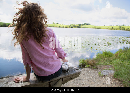 Teenage girl sitting on bench with ice skates - Stock Photo