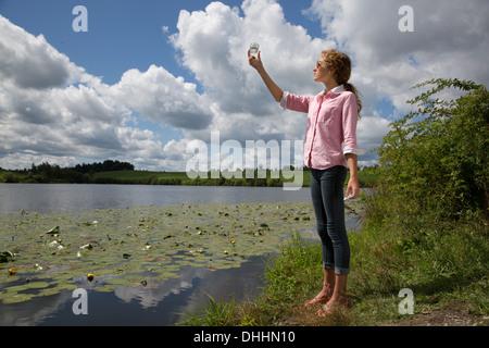 Teenage girl holding up glass jar next to lake - Stock Photo