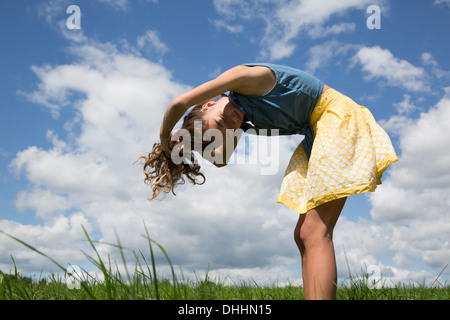 Teenage girl bending forward with hands in hair - Stock Photo