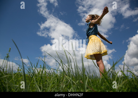 Teenage girl standing with arms outstretched in field - Stock Photo