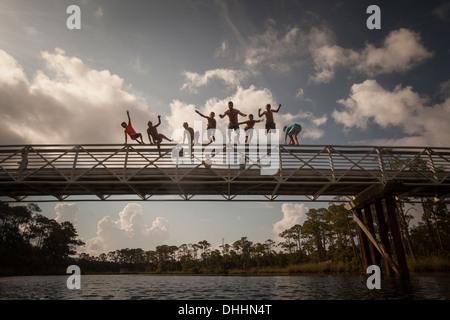 Man and children leaping from footbridge, Miramar Beach, Florida, USA - Stock Photo