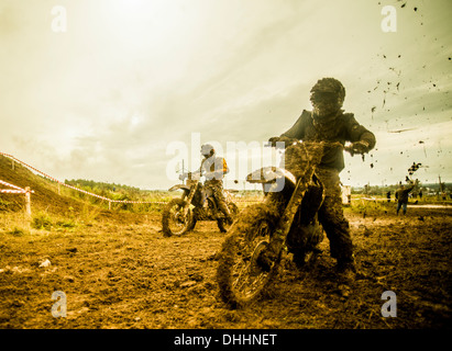 Two boys racing motorcycles at motocross - Stock Photo