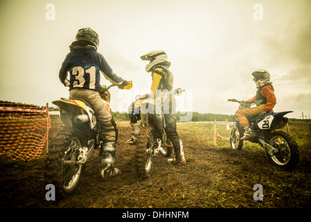 Young man and boys on motorcycles at motocross - Stock Photo