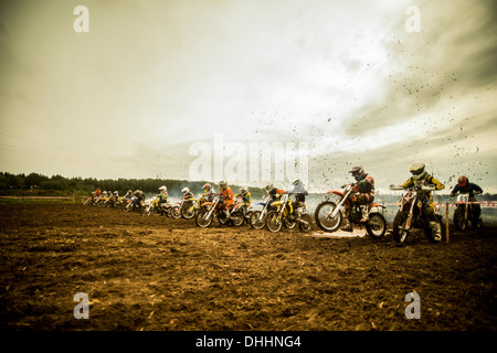 Group of boys on motorcycles at motocross start line - Stock Photo