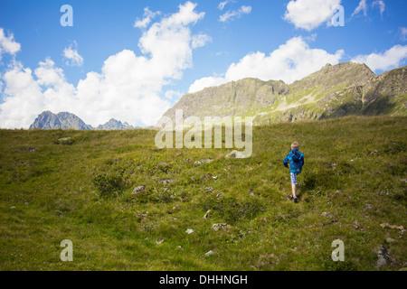 Boy walking up mountainside, Tyrol, Austria - Stock Photo