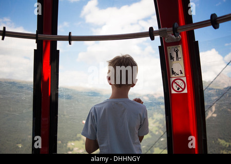 Boy looking out from cable car, Tyrol, Austria - Stock Photo