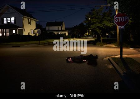 Businessman lying on suburban street unconscious at night - Stock Photo