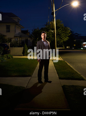 Portrait of business man coming home late at night - Stock Photo