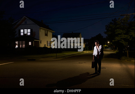 Tired business man coming home late at night - Stock Photo