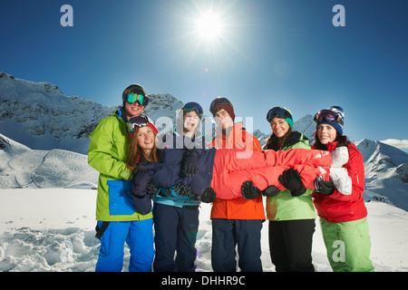 Friends holding woman in snow, Kuhtai, Austria - Stock Photo