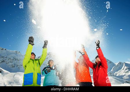 Friends throwing snow mid air, Kuhtai, Austria - Stock Photo