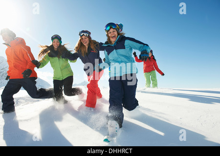 Friends running in snow, Kuhtai, Austria - Stock Photo