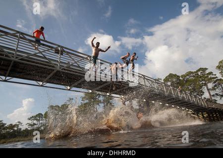 Boys and man leaping from footbridge, Miramar Beach, Florida, USA - Stock Photo