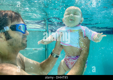 Father holding baby daughter underwater - Stock Photo