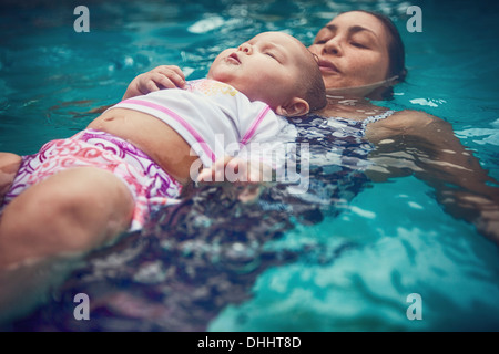Mother and baby daughter floating on backs in water - Stock Photo