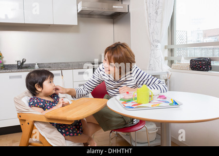Mother chatting to baby at dining table - Stock Photo