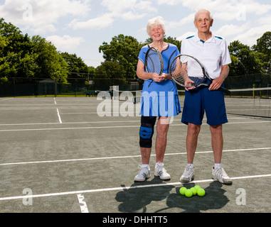 Senior couple on tennis court - Stock Photo