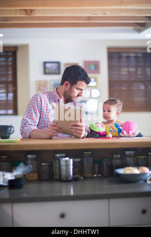 Man and baby sitting at kitchen counter looking at digital tablet - Stock Photo