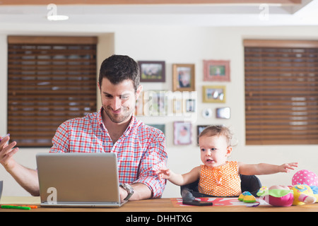 Man working at kitchen counter with baby sitting beside - Stock Photo