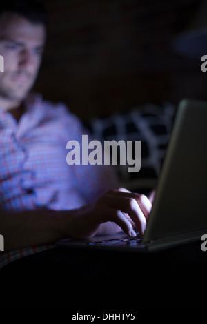 Man sitting on sofa using laptop - Stock Photo