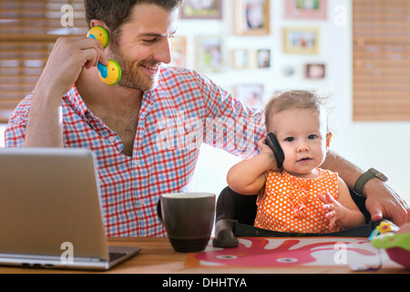 Man and baby sitting at kitchen counter playing with smartphone and toy phone - Stock Photo