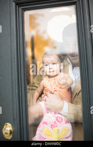 Man holding baby looking through front door
