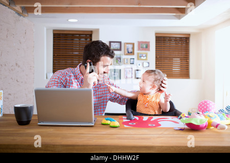 Man and baby sitting at kitchen counter making phone call - Stock Photo
