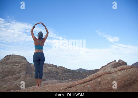 Woman doing yoga at Vazquez Rocks, hands together above her head - Stock Photo