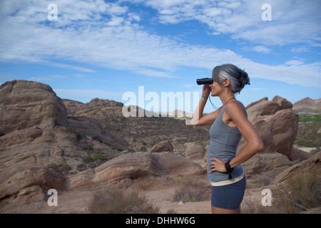 Woman standing at Vazquez Rocks looking through binoculars - Stock Photo