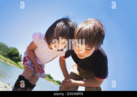 Boy and girl looking down at something - Stock Photo