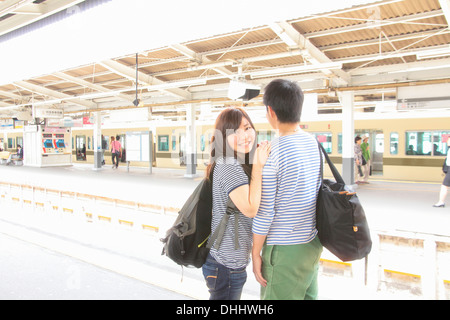 Young couple on platform at train station - Stock Photo