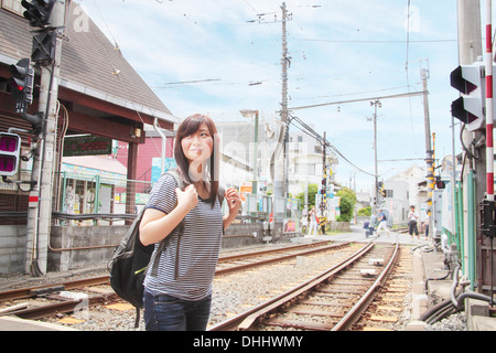 Young woman crossing level crossing over train tracks - Stock Photo