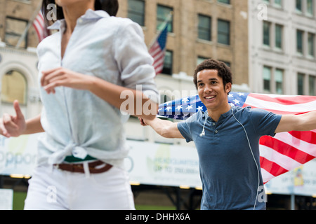 Man with American flag running after woman - Stock Photo