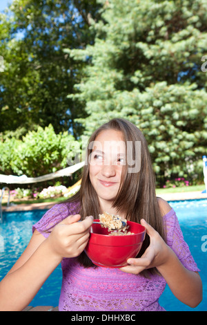 Girl eating by pool - Stock Photo