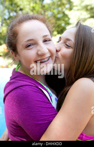 Friends hugging and kissing on cheek - Stock Photo