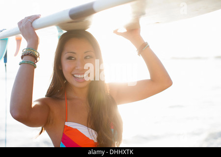 Young woman carrying surfboard, San Diego, California, USA - Stock Photo