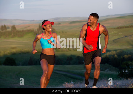 Young couple running in landscape, Othello, Washington, USA - Stock Photo