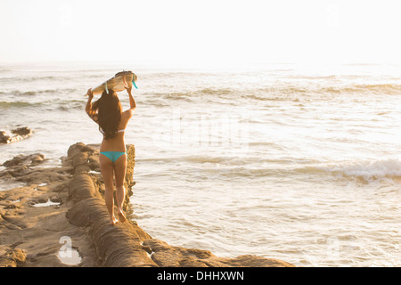 Young woman holding up surfboard, San Diego, California, USA - Stock Photo