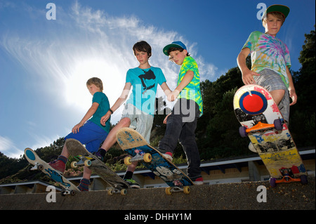 Portrait of four boys on skateboards - Stock Photo