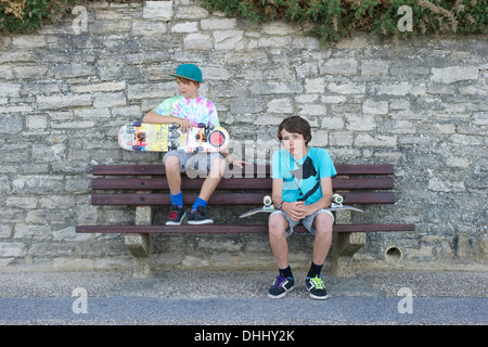 Portrait of two boys sitting on bench holding skateboards - Stock Photo