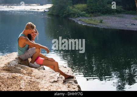Young couple sitting on rock ledge, Hamburg, Pennsylvania, USA - Stock Photo
