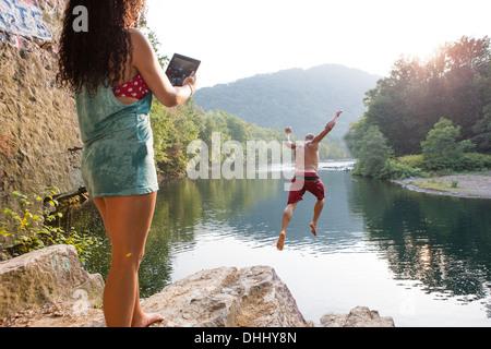 Woman photographing boyfriend jumping from rock ledge, Hamburg, Pennsylvania, USA - Stock Photo