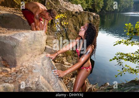 Young couple on rock ledge, Hamburg, Pennsylvania, USA - Stock Photo