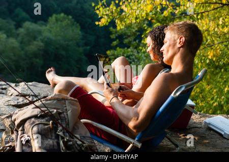 Young couple relaxing on rock ledge, Hamburg, Pennsylvania, USA - Stock Photo