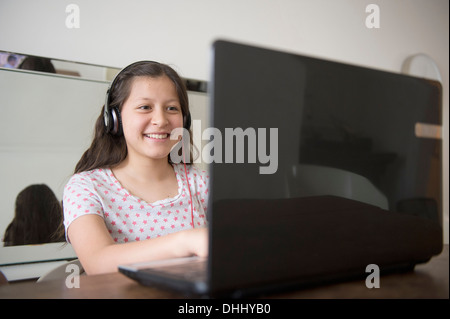 Teenage girl wearing headphones using laptop - Stock Photo